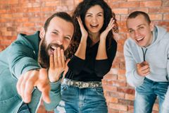 Millennials amused cheerful laughing emotional. Amused, cheerful millennial mocking. Young emotional people laughing, having fun together. Hipster guy pointing stock image