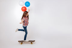 Amused child skateboarding in the studio. Practicing new skills. Skillful gifted artistic child expressing joy and holding colorful balloons while standing Stock Photography