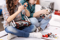 Amused children constructing gadgets and devices at home. Cooperation in details. Smiling positive merry friends sitting at home and constructing gadgets and stock image