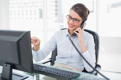 Amused classy brown haired businesswoman answering the telephone Stock Photography