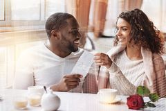 Amused couple spending delightful time together. Journey waiting. Positive men presenting flight tickets to his girlfriend while looking at her with love and stock photography