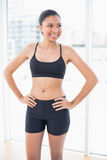 Amused dark haired model in sportswear posing with hands on the hips Royalty Free Stock Photos
