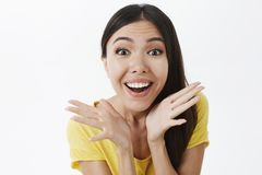 Amused and excited happy enthusiastic woman with dark hair in yellow t-shirt holding palms near face and smiling. Impressed being delighted with awesome product royalty free stock photography