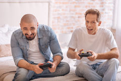 Amused friends playing with game console on the bed. Full of fun. Delighted smiling male friends holding game consoles while sitting on the bed and expressing royalty free stock images