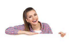 Amused Girl Behind Banner. Laughing beautiful young woman in lumberjack shirt leans on a white banner and looking at camera. Head and shoulders studio shot on royalty free stock photography