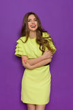 Amused Girl In Elegant Lime Dress. Laughing beautiful young woman in lime green dress posing with arms crossed and looking at camera. Three quarter length studio stock image