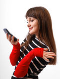 Amused girl with mobile phone close-up. Laughing teenage girl with mobile phone, expressive gesture of arms in red sleeves royalty free stock image