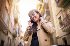 Amused girl. A photo of young woman in beige coat talking on the mobile and laughing royalty free stock photos