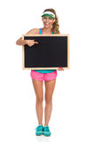 Amused Girl Pointing At Blackboard. Laughing beautiful young woman in pink shorts and turquoise tank top holding blackboard and pointing. Front view, Full length royalty free stock photo