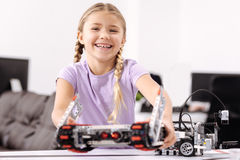 Amused girl representing science project at school. My first science project. Delighted happy joyful girl standing at school and holding robot while representing stock image