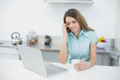 Amused gorgeous woman using her notebook while holding a cup Royalty Free Stock Images