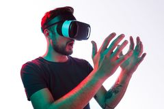Amused guy exploring virtual world. Young tattooed man wearing glasses of virtual reality looking at invisible object in hands on white background stock photography
