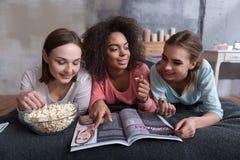 Amused ha fatto partecipare le ragazze che leggono la rivista a casa Fotografia Stock