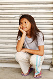 Amused homeless child. Homeless poor girl sitting on the sidewalk watching something with a smile stock image