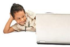 Amused kid. Kid being amused, watching cartoon on laptop Royalty Free Stock Image