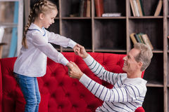 Amused little girl having fun with her grandfather Stock Image