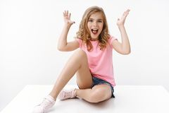 Free Amused Lively Enthusiastic Cute Blond Girl, Sit On Floor Shaking Raised Hands Excited, Smiling And Scream Childish Royalty Free Stock Photography - 160903127