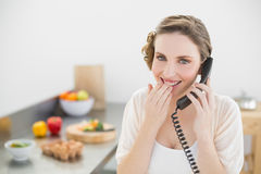 Amused lovely woman sitting in her kitchen phoning with a telephone Stock Photo