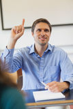 Amused male mature student raising his hand. Sitting in classroom Royalty Free Stock Image