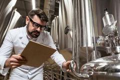 Amused man checking brewing mechanism. Make it work. Amused handsome young man checking brewing mechanism while working at factory and making notes Royalty Free Stock Images