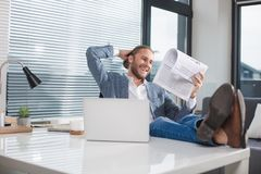 Amused man looking at journal with joy. Smiling guy relaxing in the office with mug of beverage. He is reading newspaper with happiness stock photos