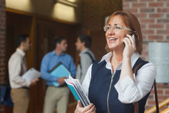 Amused mature student phoning standing in corridor Royalty Free Stock Photo