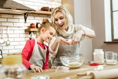 Amused mother being happy with interest of her daughter. Mother showing separating. Amused mother being happy with interest of her daughter to cooking process stock image