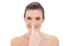 Amused natural brown haired model touching her nose Royalty Free Stock Image