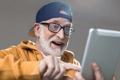 Entertained stylish senior using tab royalty free stock photo