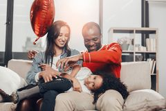 Amused parents relaxing on couch and titillating daughter. Glad mom and dad having fun with kid. They are resting on divan and tickling girl while happy child is royalty free stock image