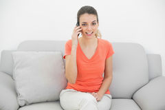 Amused ponytailed woman phoning looking at camera. Sitting on couch royalty free stock image