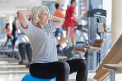 Amused pretty gray haired training in a gym. Stock Images
