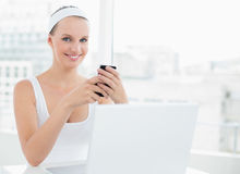 Amused pretty sportswoman sending texts Royalty Free Stock Image