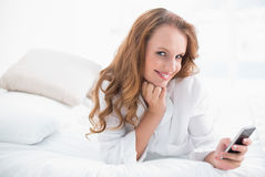 Amused pretty woman using her mobile phone on her bed Stock Photography