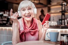Amused short-haired old woman wearing bright silk top royalty free stock photo