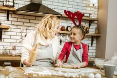 Amused short-haired woman looking on happy daughter. Mini rolling pin. Amused short-haired women looking on happy daughter while she spreading dough on table stock image