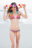 Amused slim brown haired model in coloured bikini playing with a flower necklace Stock Photography