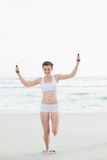 Amused slim brown haired model in white sportswear playing with a skipping rope Royalty Free Stock Images