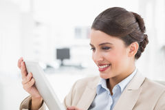 Amused smart brown haired businesswoman looking at a tablet pc Royalty Free Stock Image