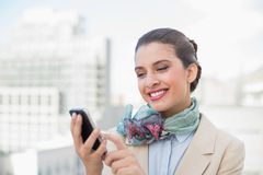 Amused smart brown haired businesswoman using a mobile phone Royalty Free Stock Photo
