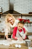 Amused smiling mother attentively looking on diligence of her kid. Covered in flour. Amused smiling mother attentively looking on diligence of her kid in baking royalty free stock images