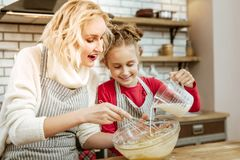 Amused surprised blonde woman looking on her daughter. Preparing baking mixture. Amused surprised blonde women looking on her daughter while she pouring milk royalty free stock photography