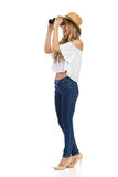 Amused Woman Looking Through Binoculars. Blond young woman in straw hat, jeans and white shirt is looking through binoculars and shouting. Side view. Full length royalty free stock image