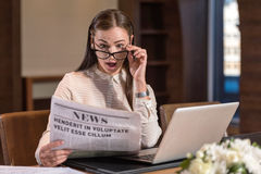 Amused woman reading newspaper in an office Stock Image