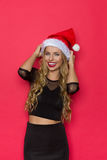 Amused Woman In Santa Hat. Laughing young blond woman in santa hat and black dress. Waist up studio shot on red background stock photography