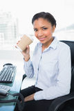 Amused young dark haired businesswoman drinking coffee Royalty Free Stock Images