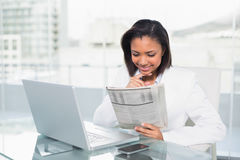 Amused young dark haired businesswoman reading a document Stock Photos