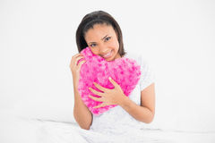 Amused young dark haired model cuddling a heart-shaped pillow Royalty Free Stock Images