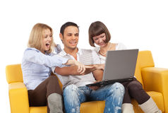 Amused young people. Three amused people with laptop computer sit on yellow sofa royalty free stock photos