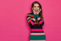 Amused Young Vibrant Woman Is Holding Head In Hands. Excited beautiful young woman in colorful vibrant striped dress is holding head in hands, looking at camera Stock Photos